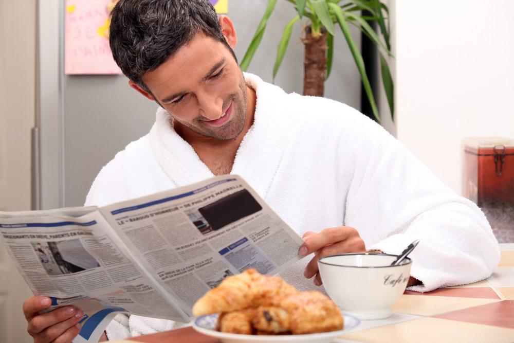 Beim Fruehstuecken einen spannenden Zeitungsartikel lesen. (Bild: auremar / Shutterstock.com)